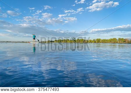 solo stand up paddler on a calm lake in summer morning - Boyd Lake State Park in northern Colorado