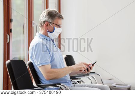 Mature Man With Face Mask Sitting In A Bright Waiting Room Looking At Smartphone