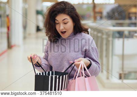Brunette Girl Looking Inside Of Opened Shopping Bag And Sees Superfluous Thing, Being Pleasantly Sur
