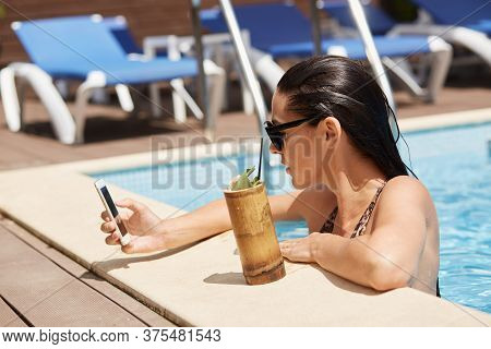 Beautiful Young Woman Posing At Poolside While Drinking Cocktail And Checking Her Social Network Via