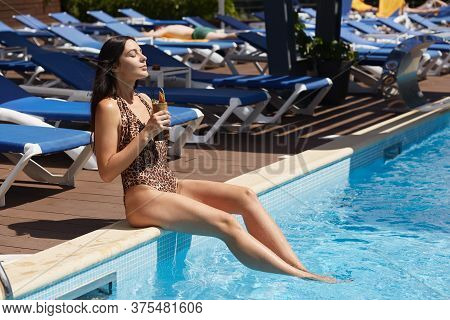 Relaxing Woman Wearing Stylish Swimwear With Leopard Print Enjoying Fresh Cocktail While Sitting At