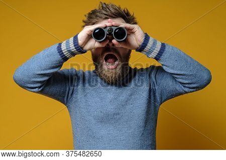 Surprised Shaggy, Bearded Man In A Stratum Sweater Looks Through Binoculars With Mouth Open.