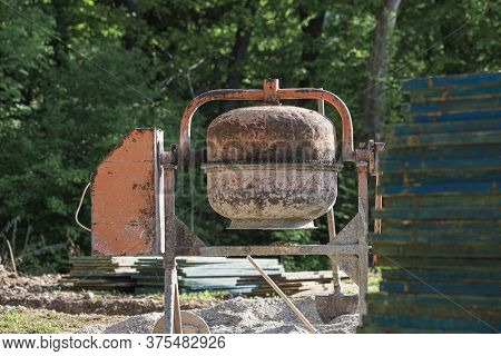 Cement Mixer, Building Supplies And Stack Of  Wooden Panels Outside In Construction Site.