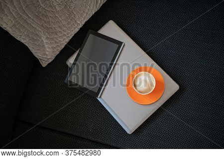 Top View Of Digital Tablet And Cup Of Coffee On Top Of Laptop Computer Lying On The Couch.