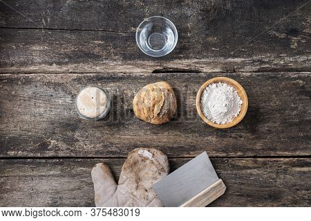 Top View Of Still Life With Homemade  Sourdough Bread Bun And Ingredients - Water, Starter Yeast And