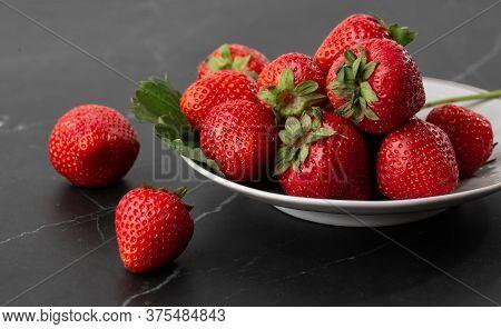Fresh Strawberries In Plate On Marble Black Table. Fresh Nice Strawberries. Strawberry Field On Frui
