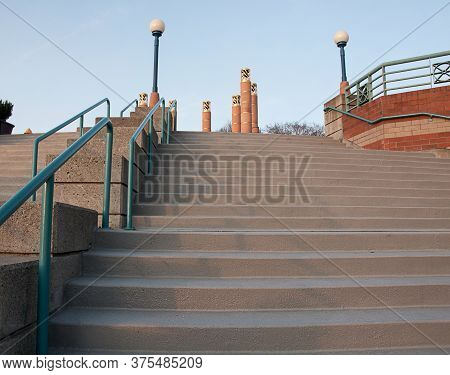 Outdoor Stairway With Lamp Posts With Decorative Posts Near The Top Against A Blue Sky.