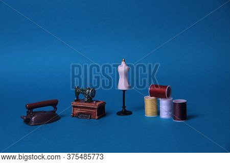 Sewing Machine, Tailor's Dummy, Skeins Of Thread For Needlework, Iron On Blue Background. Image Cont