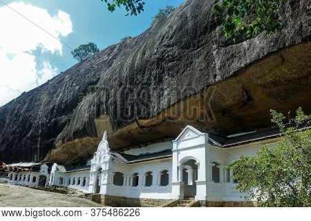 The Ancient Cave Temple Of Dambulla, Sri Lanka. Stone White Facade Of The Building With Carved Windo