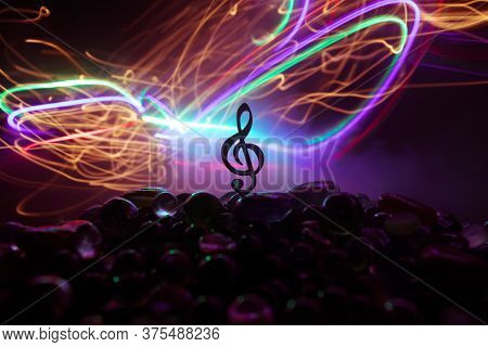 Musical Symbol Treble Clef Stainless Steel Miniature With Colorful Toned Light On Foggy Background.