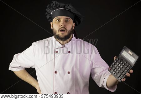 Astonished Young Bearded Male Chef Cook In Uniform Holding Calculator Shows Results Of Calculations