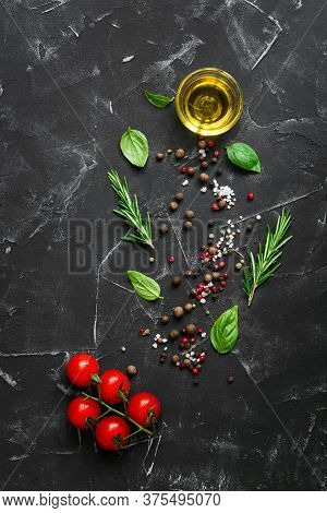 Black Stone Culinary Background With Seasonings, Spices, Vegetables, Oil. Cherry Tomatoes, Basil, Ro