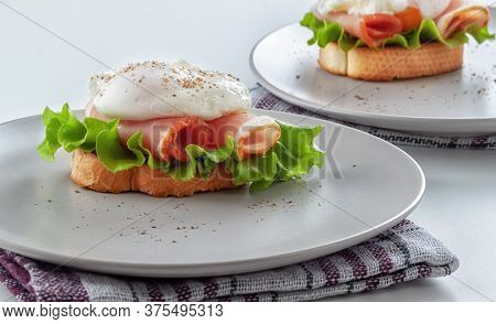 Benedict Eggs On A Toasted Baguette With Bacon And Salad And On A Platter