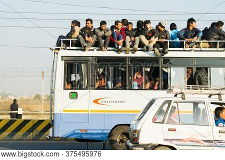 Kathmandu, Nepal - 22 Nov 2015: Commuters Pack Into And On Top Of The Rare Buses Still Serving The C