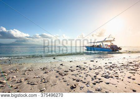 Bali, Indonesia - 5 Aug 2019: A Motor Boat Used For Scuba Diving In Moored On A Pebble Beach At Sunr