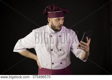 Upset Astonished Young Bearded Master Chef In Uniform Looking At Calculator Isolated On Black. Resta