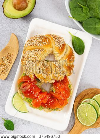 Sliced Salmon With Avocado On Bagel With Sesame Seeds On Gray Stone Background. Top View. Perfect He
