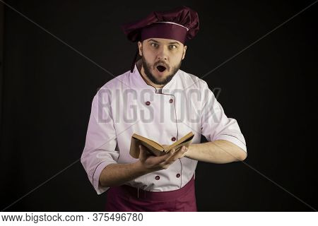 Astonished Young Bearded Master Chef In Uniform Keeps Open Book Of Vintage Old Recipes Looking At Ca