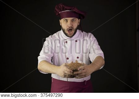Astonished Young Bearded Master Chef In Uniform Holding Bowl Of Cereal Looking At Camera Isolated On