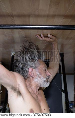 Mature Man Using Inversion Table At  Gym