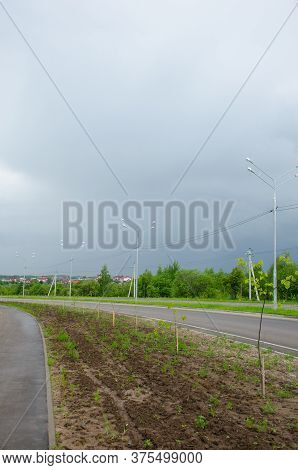 Vertical Photo Of A New Stretch Of Road Outside The City. The Pedestrian Zone And The Carriageway Ar