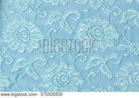 Blue Lace Texture With Flowers On A Blue Background. Background Of Blue Lace With A Floral Pattern O