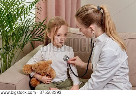 Child Behaves Obediently. The Doctor Listens To Patient With A Phonendoscope.