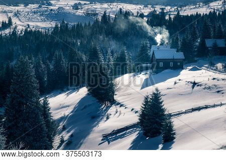 Small Houses With Smoke In The Chimney On A Cold Winter Morning In Marisel, Cluj County, Transylvani