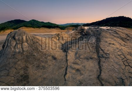 Panorama Shot Of Some Of The Craters At Muddy Volcanoes In Romania, Buzau County With The Mountains