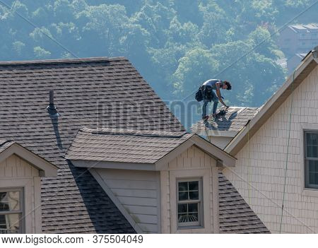 Morgantown, Wv - 8 July 2020: Young Roofing Contractor Replacing The Old Shingles On A Townhouse Roo