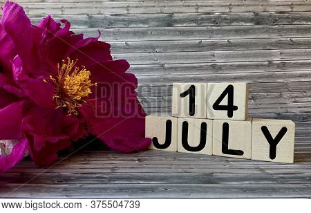 July 14. July 14 On Wooden Cubes On A Wooden Background.peonies.photos For The Holiday .