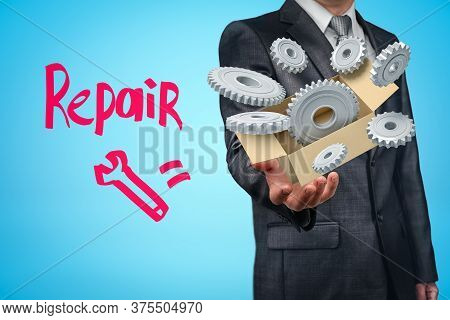 Businessman Holding Cardboard Box Filled With Grey Gear Wheels And Repair Sign On Blue Background