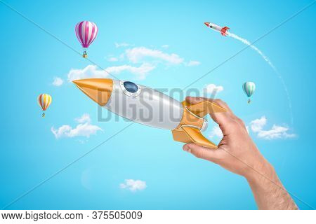 Mans Hand Holding Silver And Yellow Space Rocket Against Bright Blue Sky With Hot Air Balloons And O
