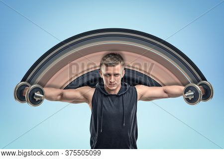 Strong Muscular Young Man In Black Sportswear Holding Two Dumbbells On Blue Background
