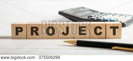 The Word Project Is Written On Wooden Cubes Between A Pen And A Calculator On A Light Table. Busines