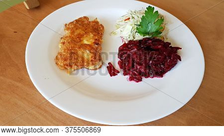 Pork Chop And Salad Of Finely Chopped Cucumbers And Beets On A Plate