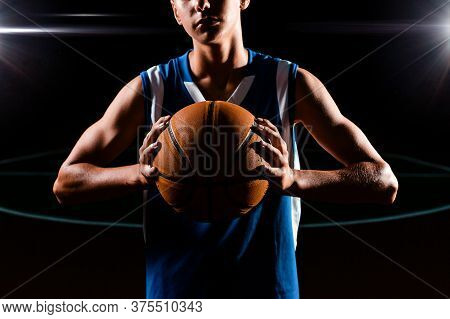 Basketball. Close Up Portrait Of A Teenage Boy In Blue Sportswear Confidently Holds A Basketball Wit