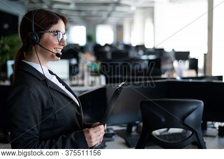Female Helpdesk Operator Stands With A Folder In Her Hands. An Office Manager With A Headset Answers