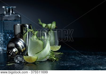 Gin Tonic With Rosemary, Lime And Cucumber In Frosted Glass. Cocktail On A Dark Background.