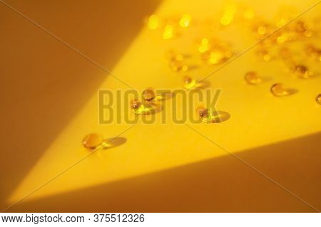 Gelatin Capsules In A Ray Of Light On A Yellow Background. Dietary Supplement, Health Care, Soft Foc