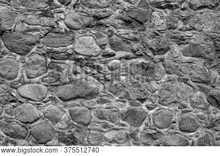 Monochrome Stone Wall Texture Background. Fragment Of A Massive Wall Of An Ancient Building.