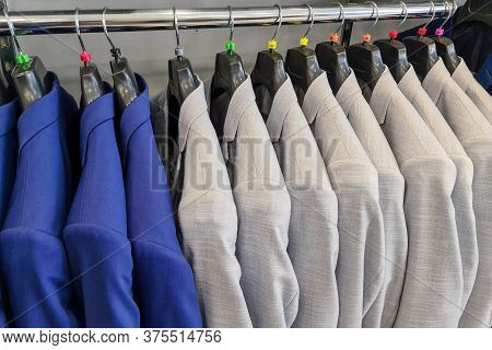 Men Row Of Blue And White Suits On Hanger. Men Clothes Hanging On Wooden Hangers In A Store. Men's S