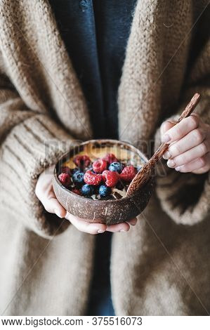 Healthy Vegan Breakfast Bowl With Oats, Berries In Womans Hands