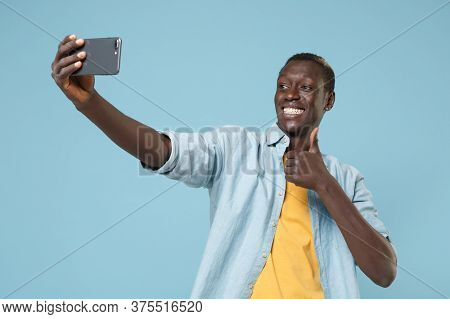 Smiiling Young African American Man Guy In Casual Shirt, Yellow T-shirt Isolated On Blue Background.