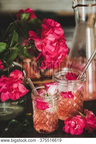 Rose Lemonade With Ice And Petals Over Kitchen Counter, Close-up