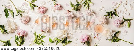 Variety Of Rose Wine In Glasses With Flowers Over Plain White Background