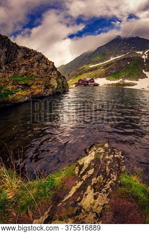 A Glacial Lake Set High Above In The Mountains Before The Snow Melted Completly With A House On The