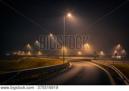 Highway Exit During A Foggy Night With Street Lights And Signs On The Asphalt