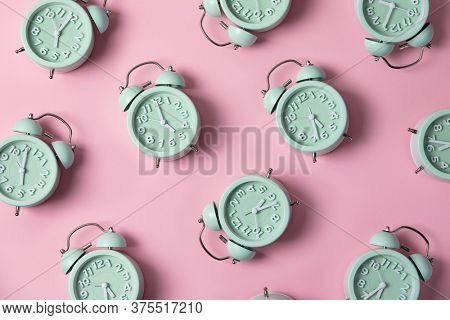 Creative layout of green alarm clock's on pastel pink background. Minimal concept. Flat lay, pattern