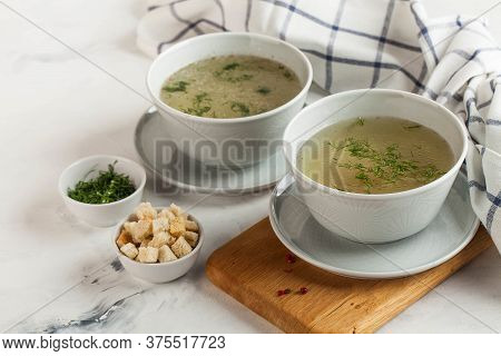 Homemade Meaty Broth With Dill In Bowls And Crackers. The Concept Of Healthy Eating. Copy Space.